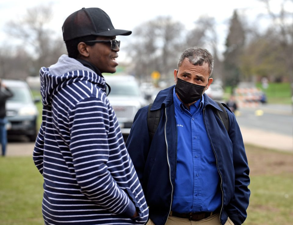 A chaplain talks with a man in a black baseball cap and striped jacket