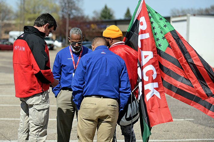 Chaplains gather in prayer with man holding Black Lives Matter flags