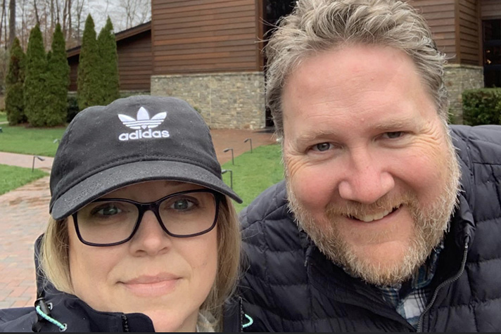 Woman and man posing for picture in front of Billy Graham Library