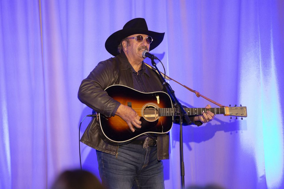 Dennis Agajanian playing guitar and singing