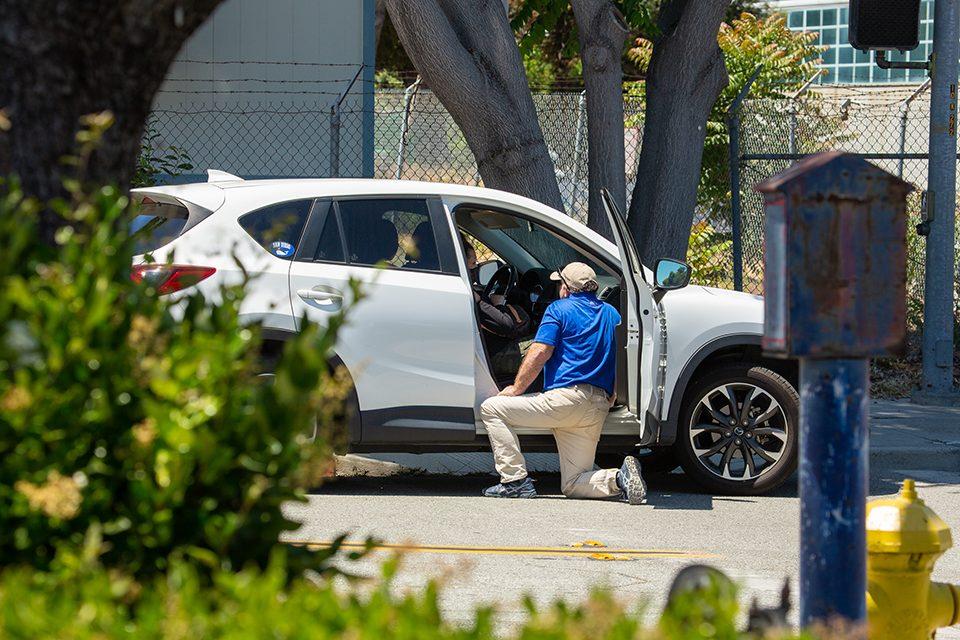 chaplain kneeling by car
