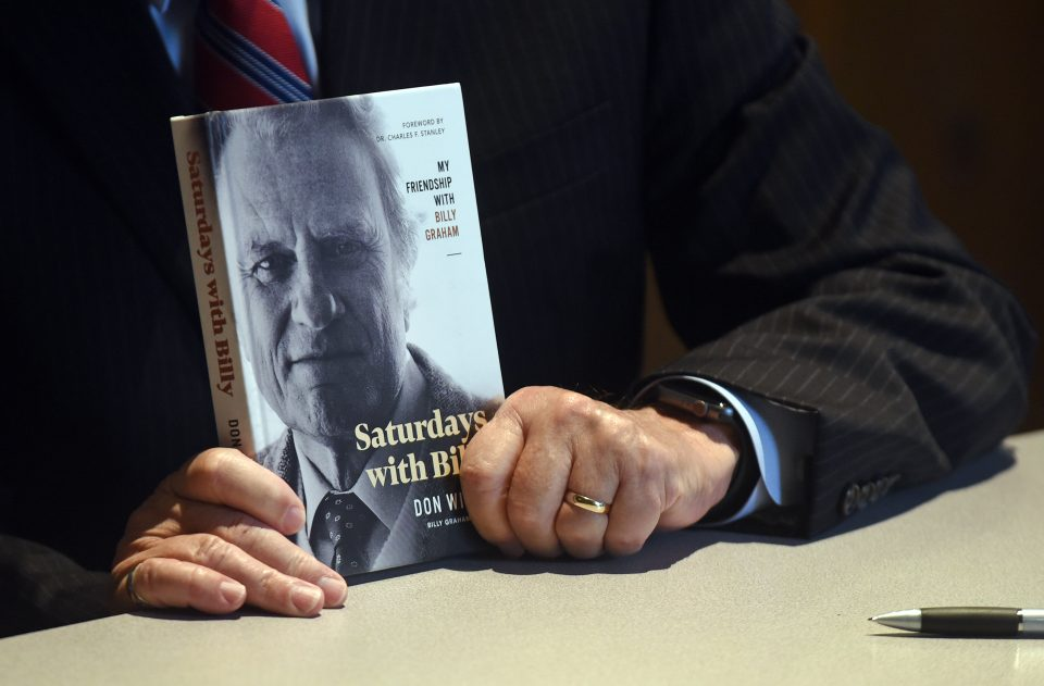 """Dr. Wilton holding copy of """"Saturdays with Billy: My Friendship with Billy Graham"""""""