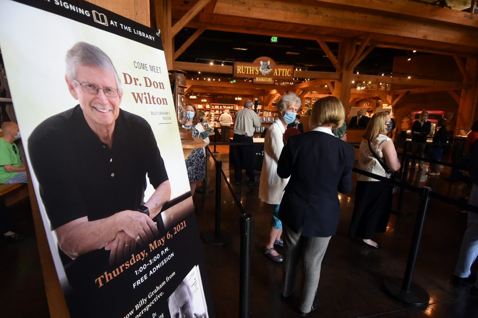 Poster promoting book signing; people in background