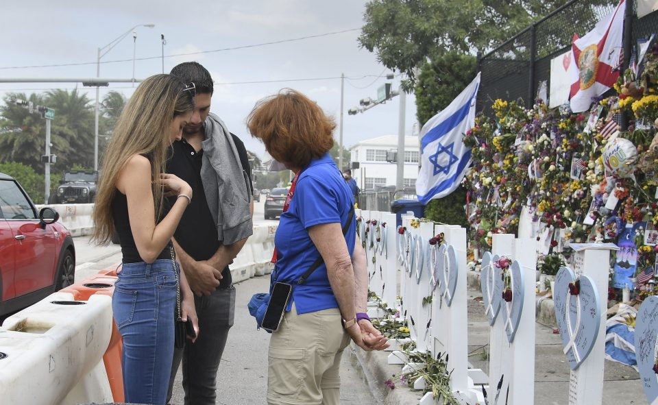 Chaplains praying with visitors to memorial for victims