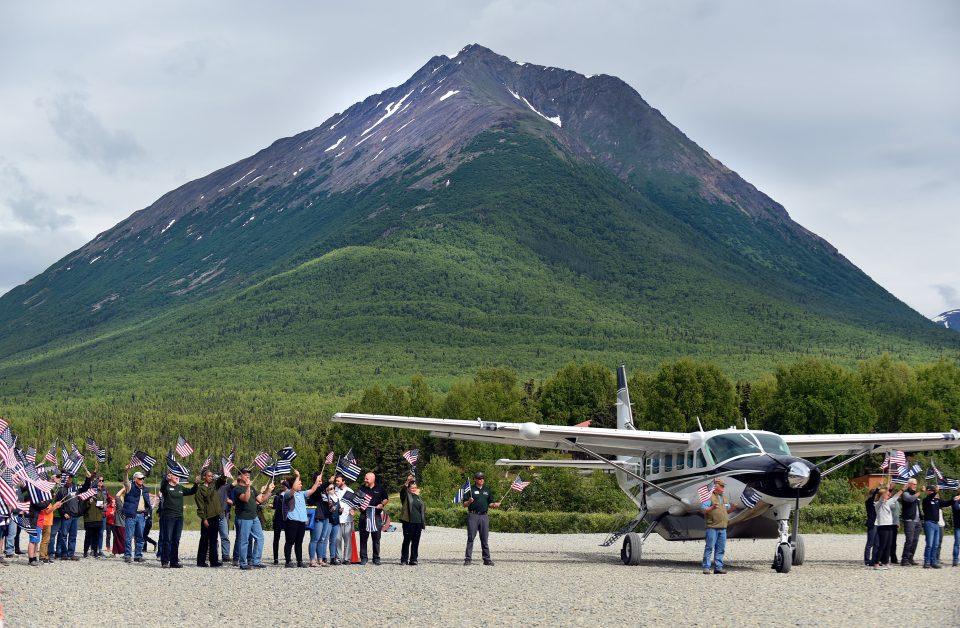 Plane on tarmac with mountain in background, people holding American flags as couples deplane