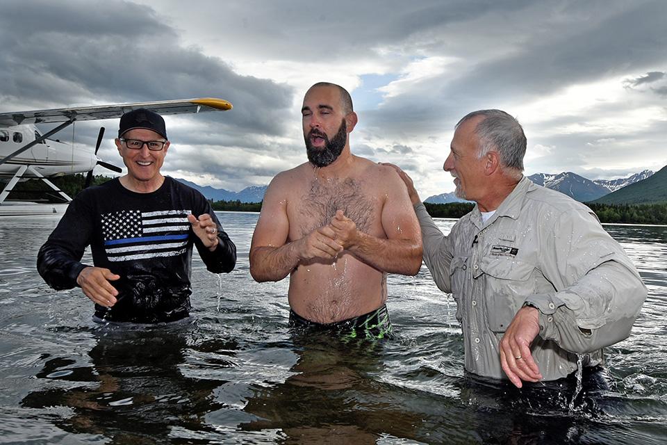Three men stand waist-deep in water, seaplane floating in background