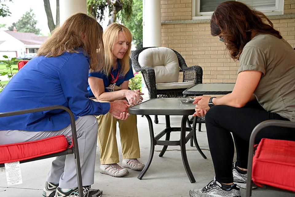 Three women praying on a porch