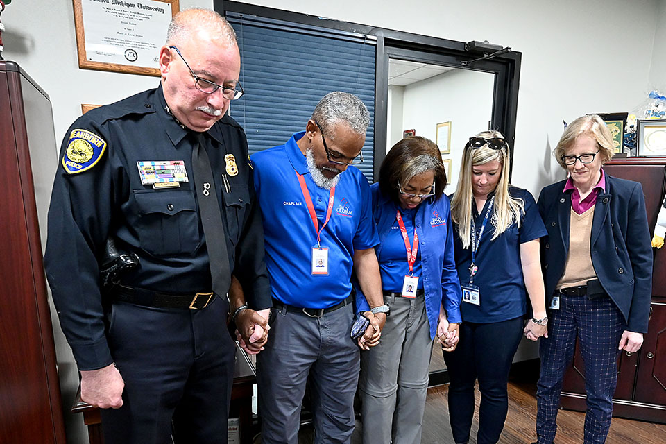 Chaplains praying hand-in-hand with chief of police and staff