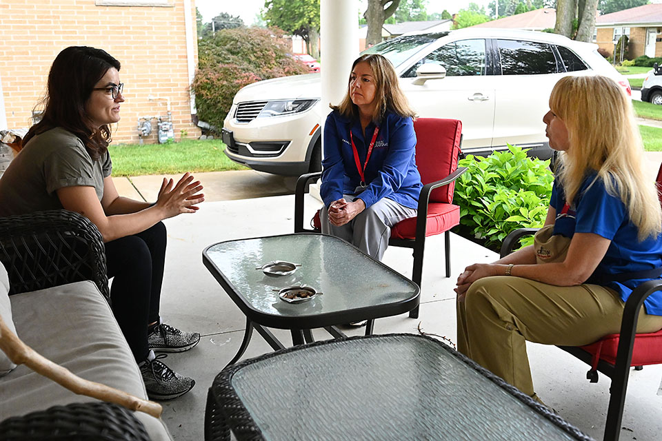 Chaplains sit with a woman on a porch