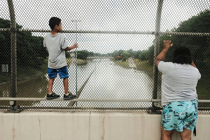 woman and child looking at flooded highway