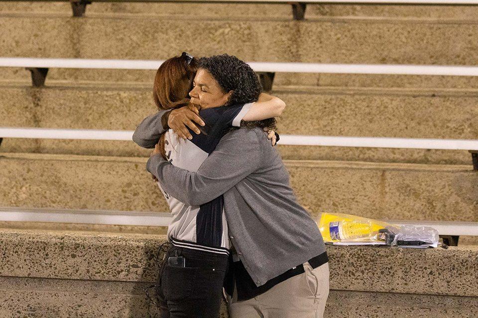 A Celebration volunteer hugging a security worker