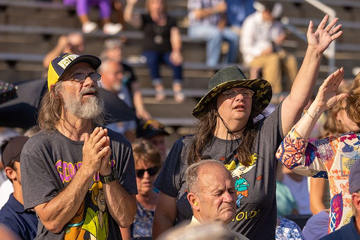Man and woman worshiping in crowd
