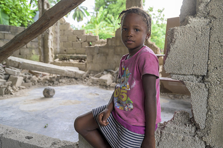 Young Haitian girl sits amid rubble