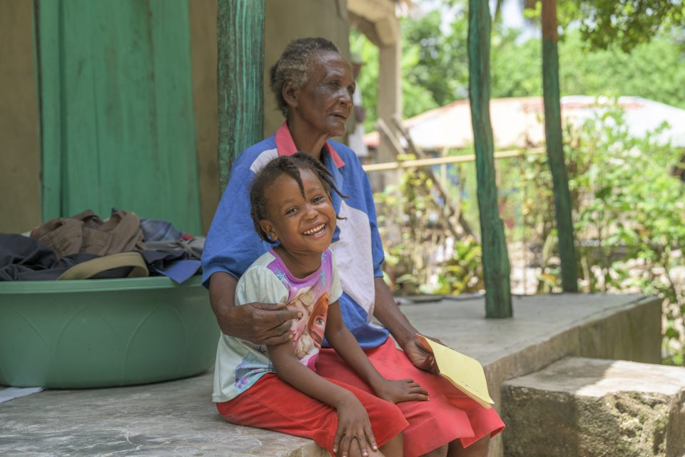 Child smiling, sitting with older woman