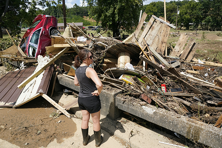 Woman standing in front of debris, wrecked car