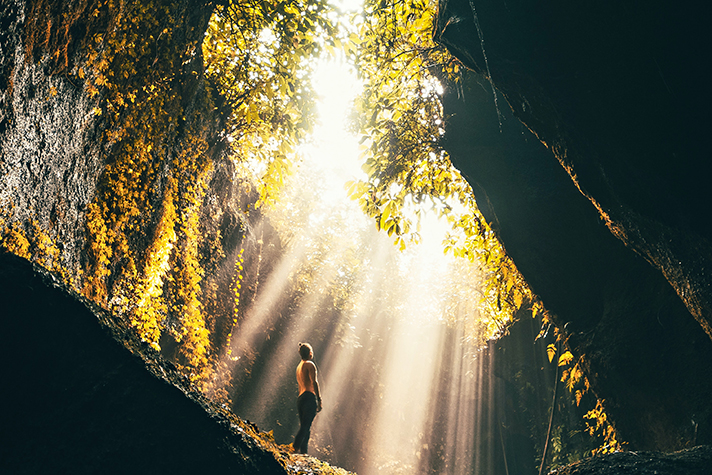 Person looking up at rays of light streaming