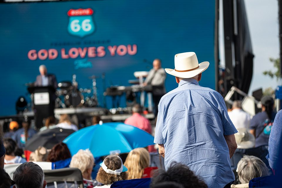 man with cowboy hat stands amidst crowd