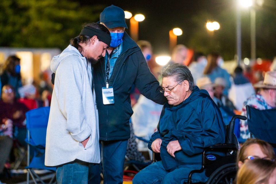 Man in wheelchair, others, Prayer Volunteer praying