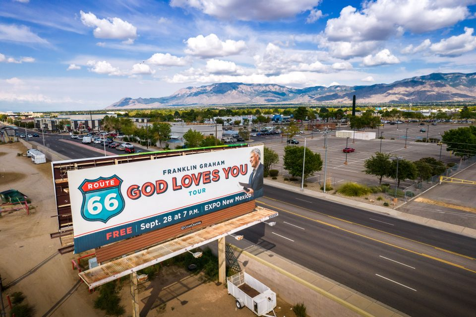 God Loves You Tour billboard set against mountains, blue sky with clouds