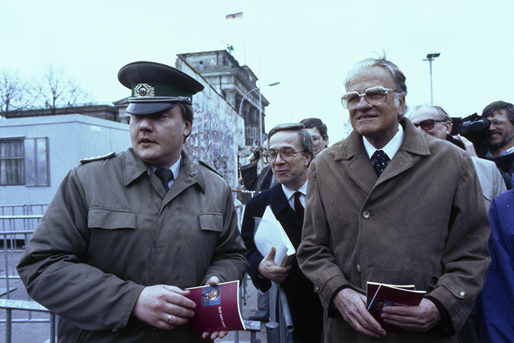 An East German officer walks with Billy Graham near the Brandenburg Gate on March 10, 1990 - four months after the opening of the Berlin Wall.