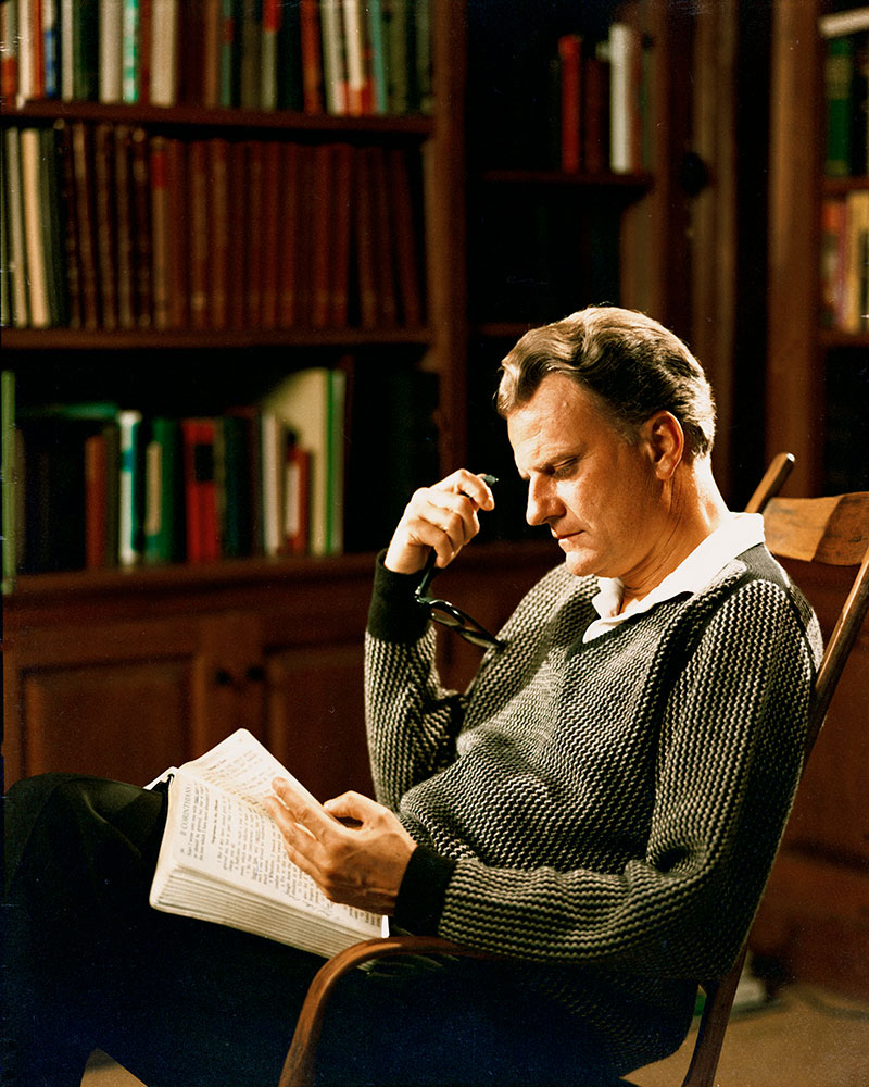 Billy Graham reading his Bible in his study
