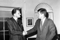 Billy Graham meets with President John F. Kennedy in 1962, on one of several occasions when Kennedy invites Graham to the White House.