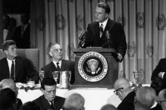 Billy Graham speaks at the National Prayer Breakfast many times, including this one in 1963. Seated to the left of the lectern are President John F. Kennedy and Vice President Lyndon B. Johnson.