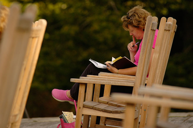 Woman on rocking chair reading bible