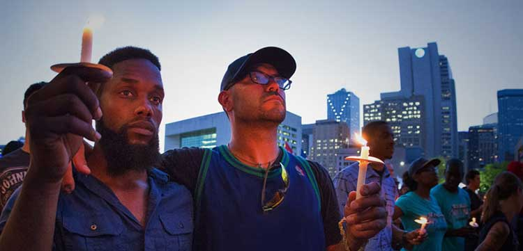 two men standing at a vigil with candles