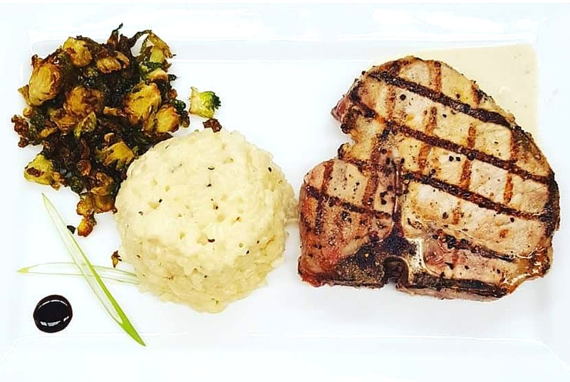 Grilled pork chop with creamy risotto and shaved brussel sprouts. Photo credit: Chef Douglas Walls